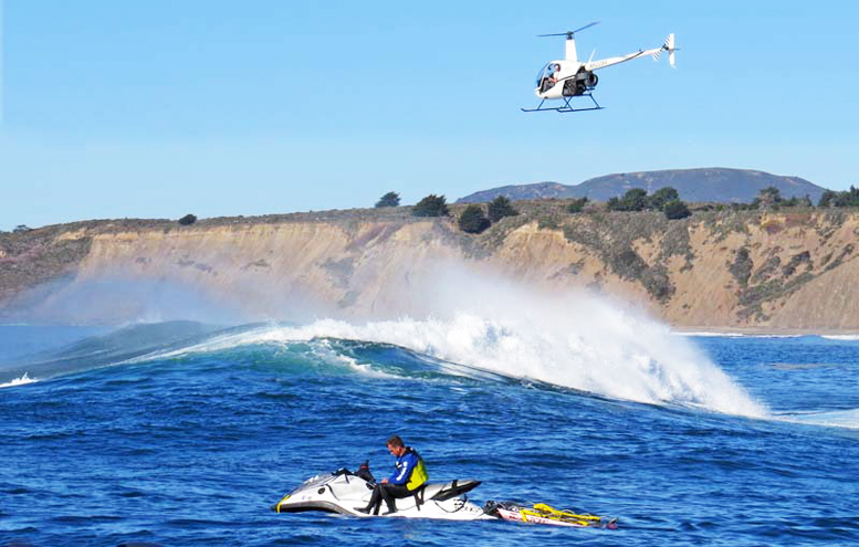 Low flying R22 helicopter over surf